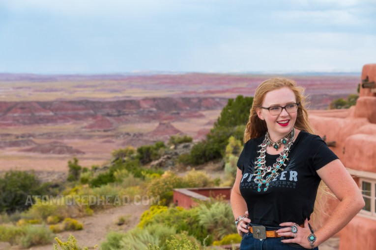 """Myself, wearing several turquoise and silver necklaces, a black t-shirt reading """"Pioneer"""" in white letters, and a jean skirt, standing in front of the Painted Desert Inn."""