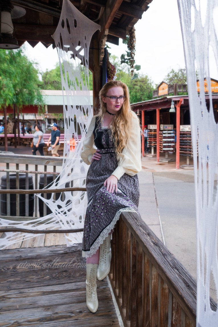 Myself, sitting on the railing of an old west building, wearing a long, black, white, and grey dress, with a black velvet bodice, and billowy white sleeves.