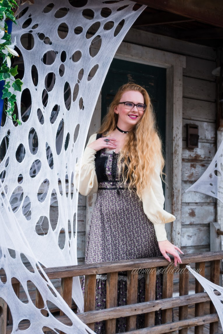 Myself, standing on the porch of a distressed old west wood building, faux cobwebs hang around the edge, wearing a long, black, white, and grey dress, with a black velvet bodice, and billowy white sleeves.