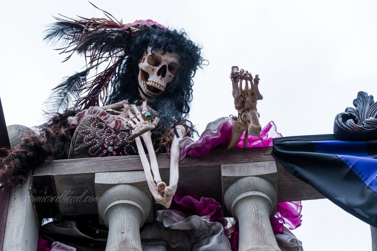 A skeleton with a black and pink can-can dress holds her leg over the rail.