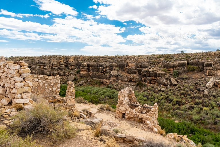 Crumbling stone walls sit near the edge of the canyon.