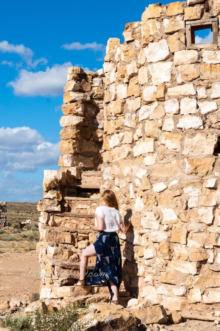 Myself, wearing a white peasant top, and a long, navy skirt with cattle skulls printed on it, and a necklace featuring a cattle skull climbing the stairs of one of the rock work ruins.