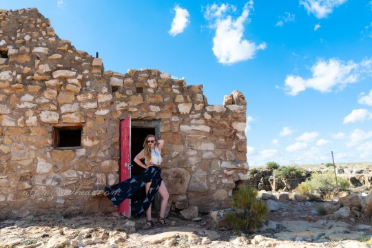 Myself, wearing a white peasant top, and a long, navy skirt with cattle skulls printed on it, and a necklace featuring a cattle skull standing in the doorway of the faux Native American ruin near the entrance to the Apache Death Cave.