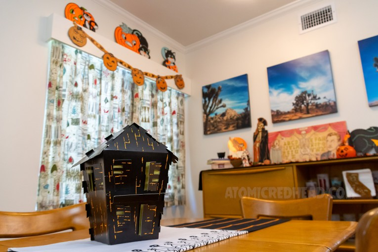 A 3D paper house sits in the middle of our dining room table. A jack-o-lantern garland hangs from the valance in the background.