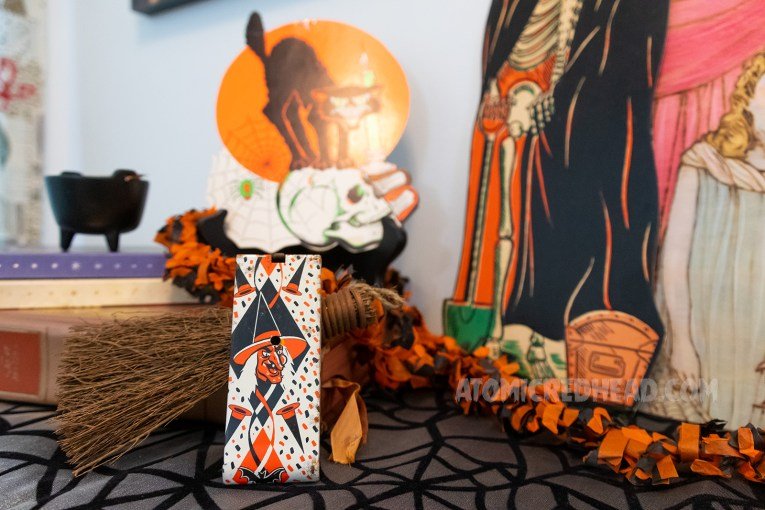 Close-up of a noise maker, white with orange and black diamond print, and a witch with a pointed hat.
