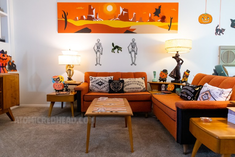 Overview of our living room. Orange and black couches sit in an L shape. An abstract desert painting hangs above the couch against the wall. Between the two are two skeletons and a black cat. Spirit board pillows sit on the couches.