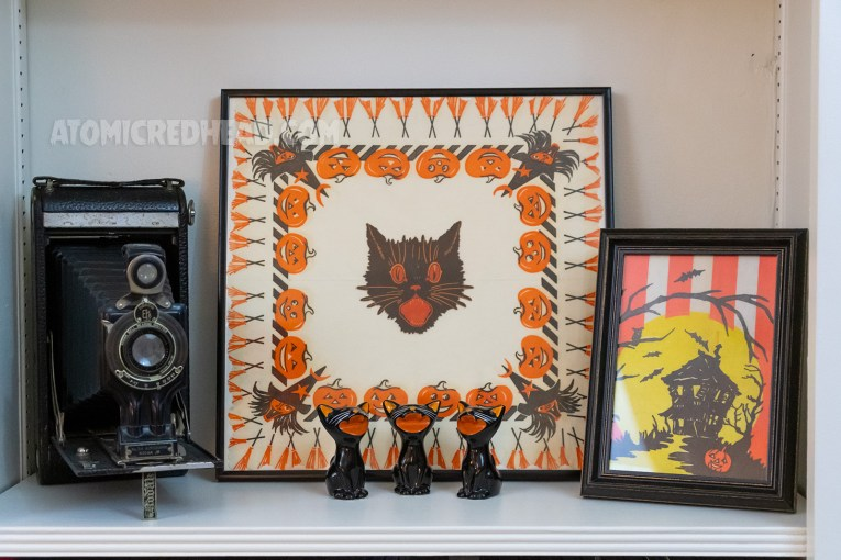 A framed napkin featuring a witch, jack-o-lanterns, and brooms with a black cat head in the middle. Three ceramic black cats sit in front. Framed to the right is a portion of a vintage table cloth featuring a haunted house.