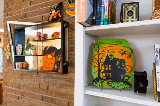 An orange, black, and green decoration of a haunted house sits on a shelf.