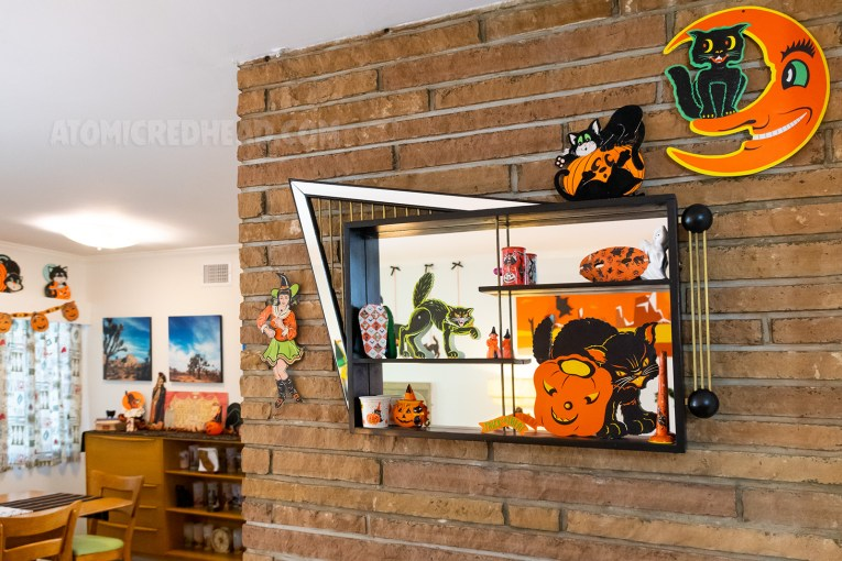 An abstract shape mirrored shadow box hangs above a fireplace. It is filled with various Halloween decorations.