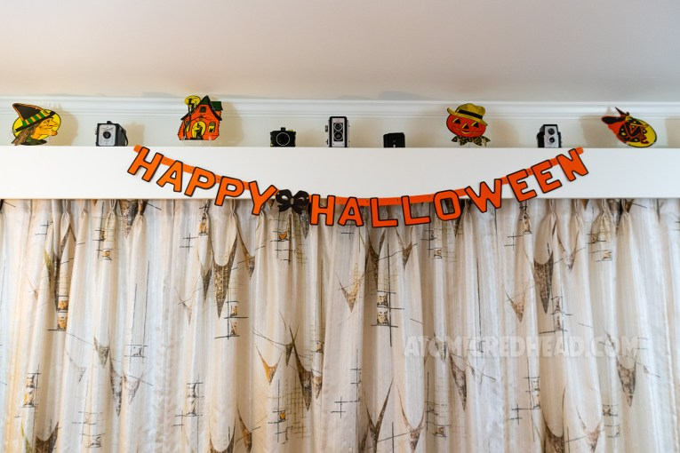"An orange and black banner reads ""Happy Halloween"" and hangs on the valance above our sliding glass door. Atop the valance are various vintage cameras, and paper Halloween decorations, including a witch, a haunted house, a jack-o-lantern with a straw hat, and a witch on a broom."