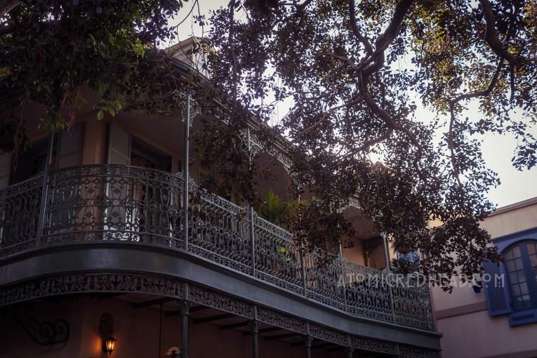 A dark green wrought iron balcony peeks from behind a tree.