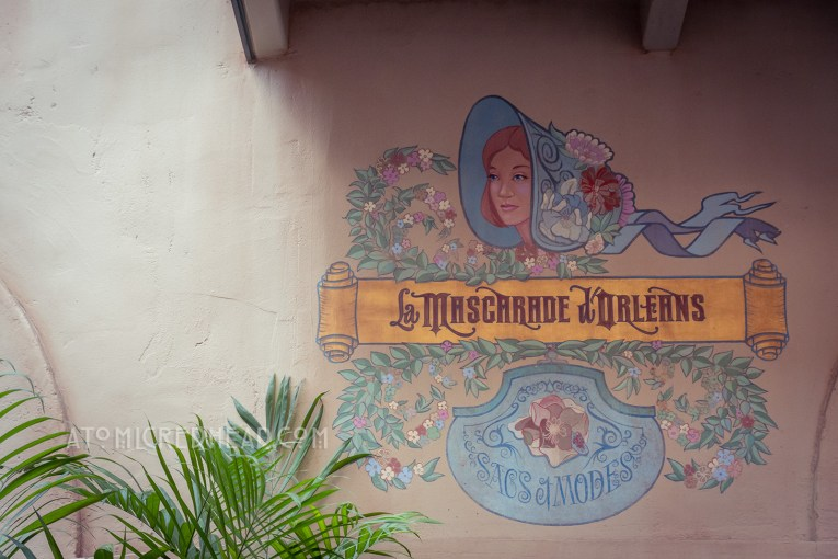 A mural advertising a shop. It features a woman wearing a bonnet and swirling ribbons and flowers.