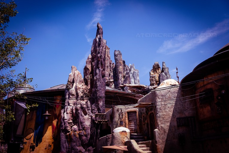 Rock spires stretch toward a blue sky. A small dwelling is nestled in the rocks.