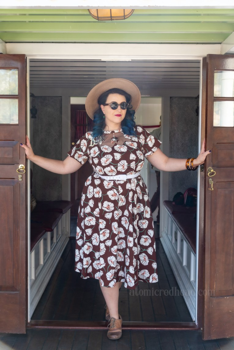 My friend Mandy stands in the doorway of a cabin on the Mark Twain. Mandy wears a brown dress with a white floral design. She has a tab wide brim straw hat, and tan and brown shoes.