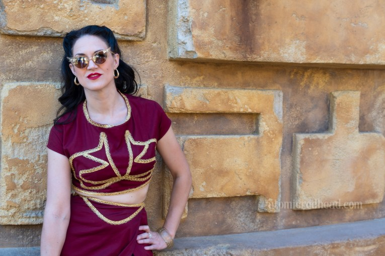 My friend Nikki wears an ensemble inspired by Princess Leia's slave ensemble. A maroon two piece. The top is cropped, and the skirt features a high slit. It is trimmed in gold. Nikki leans against a stucco wall in Star Wars: Galaxy's Edge.
