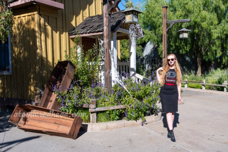 "Myself standing in front of a yellow wooden building, with wooden coffins leaning against it, wearing a black t-shirt with a circular design reading ""HEX"" in the middle. Text below reads ""Hex Girls Spell Bound World Tour 99"" with various cities listed below, a black pencil skirt, with a red belt, and black boots."
