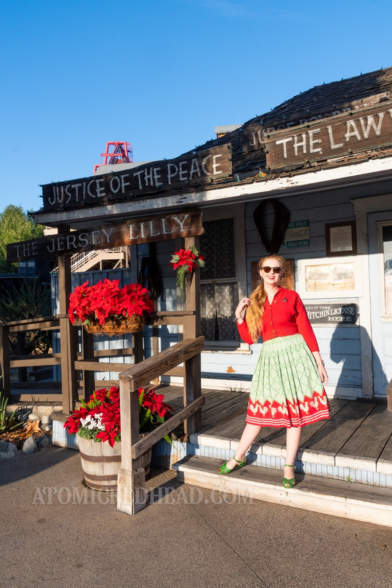 Myself, standing on the porch of a blue painted wooden western building, decorated with poinsettias, wearing a red sweater and a red and green skirt with chickens printed at the bottom.