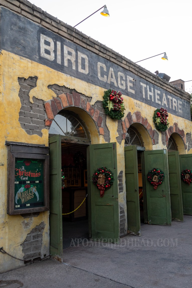 The Bird Cage Theatre, which has arched doorways, with green doors. Wreaths hang on the doors and feature small gold bird cages in the middle. A poster on the left advertises the times for the shows A Christmas Carol and Marley's Wings.
