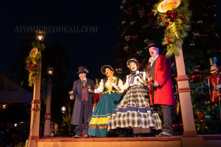 Carolers in 1800s attire sing in front of the large Christmas tree during the tree lighting ceremony.