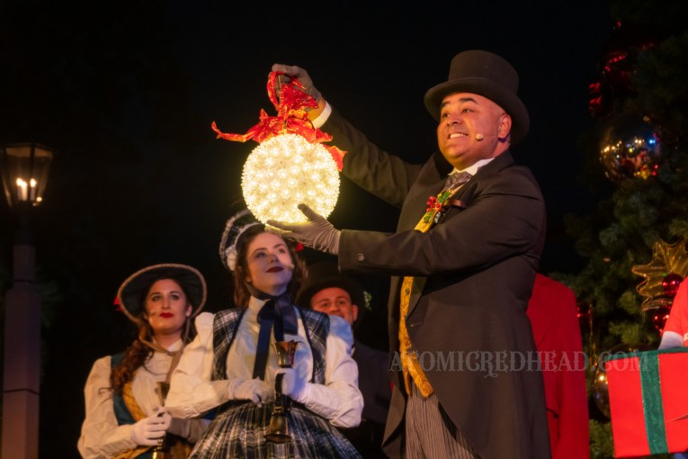 """The mayor of """"Calico"""" the area also known as Ghost Town, wears a black suit and top hat and holds a large lighted Christmas ornament."""