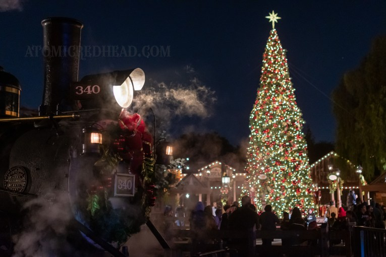 The tall, lighted Christmas tree stands behind the train, which has a wreath on the front.