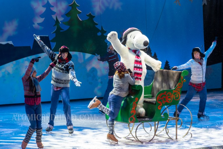 Snoopy arrives on a green sleigh in the Merry Christmas, Snoopy ice show. Various skaters in winter attire skate around him.