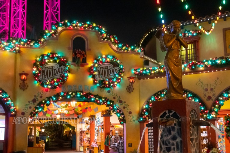"Fiesta Village is decorated with colored lights, and wreaths, inside the wreaths it reads ""Feliz Navidad"""