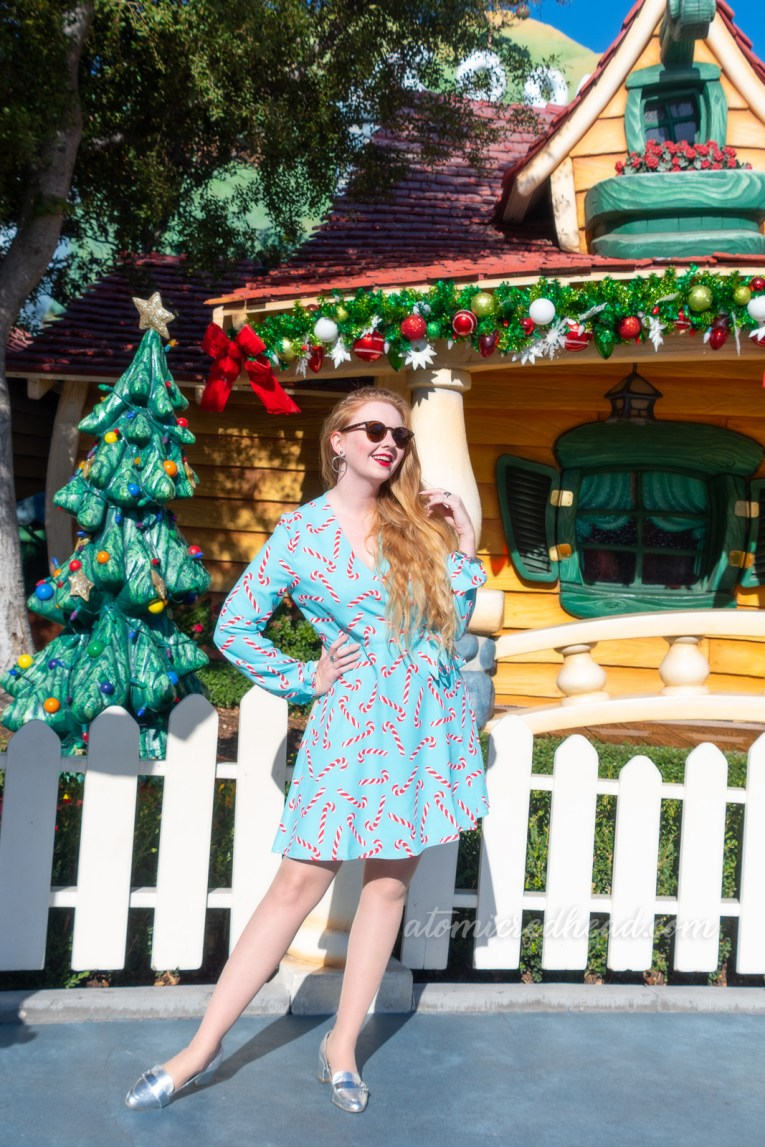 Myself standing in front of a brightly painted house, with a Christmas tree out front, wearing a short, blue wrap dress with a red and white candy cane print on it.
