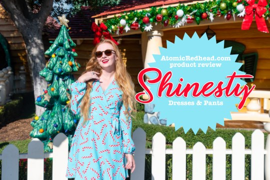 "Myself standing in front of a brightly painted house, with a Christmas tree out front, wearing a short, blue wrap dress with a red and white candy cane print on it. A blue scalloped edged circle with text on it is photoshopped into the image. Text overlay reads ""Atomicredhead.com product review Shinesty Dresses & Pants"""