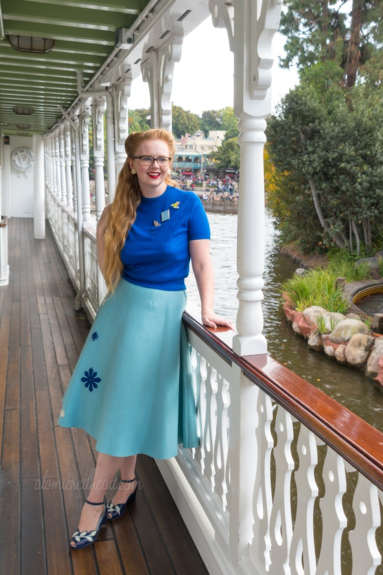 Myself, standing aboard the Mark Twain, a white paddle wheeler, looking out over the rail, wearing a bright blue sweater, and a light blue skirt with white and dark blue snowflakes sewn on.