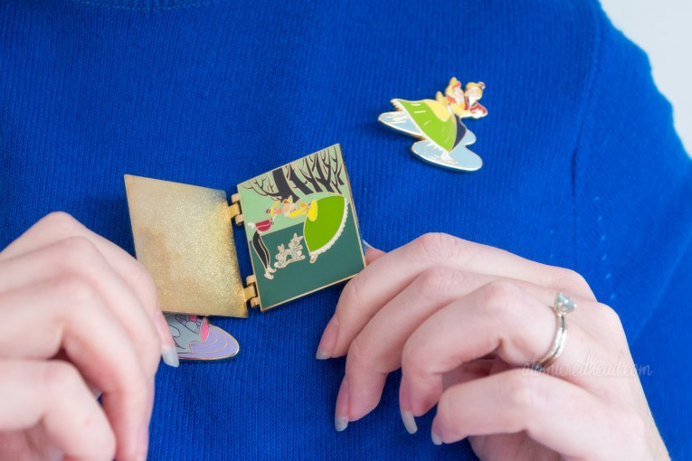Close-up of my pins, but with the book pin open, and features the couple kissing.