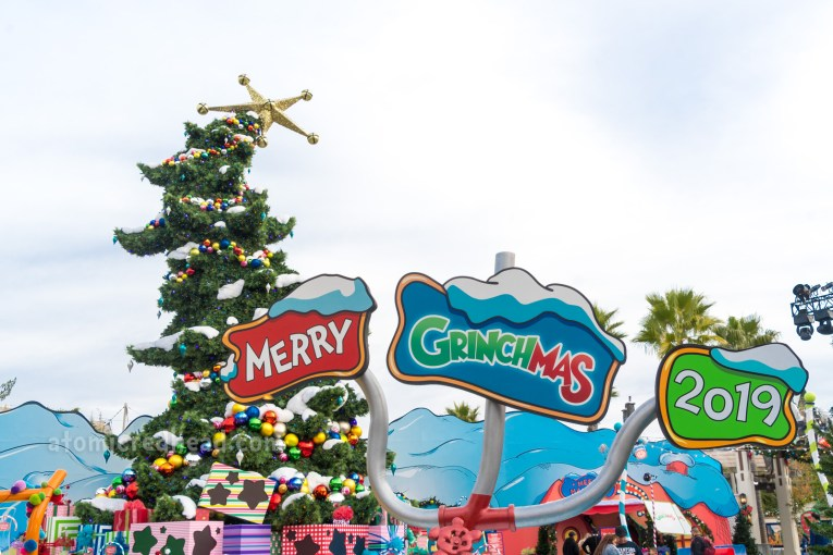 "The curling Grinchmas tree sits in the background with a sign in the foreground reading ""Merry Grinchmas 2019"""