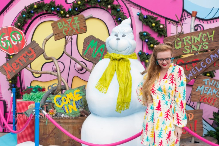 Myself, wearing a cream dress with teal, yellow, and red pine trees printed on it, standing in front of a snowman of the Grinch.