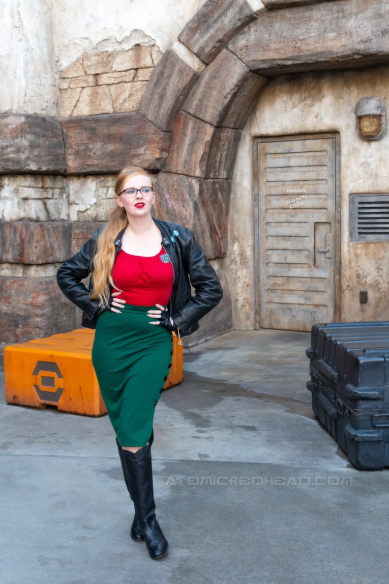 Myself, wearing a black leather jacket, with blue sabacc dice on the upper left, a red peasant top, green pencil skirt, black leather driving gloves, and black knee high leather boots, standing in front of a doorway.