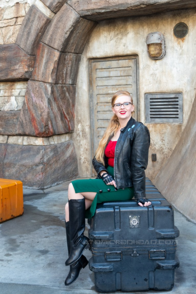 Myself, wearing a black leather jacket, with blue sabacc dice on the upper left, a red peasant top, green pencil skirt, black leather driving gloves, and black leather boots to my knee, sitting on a crate.