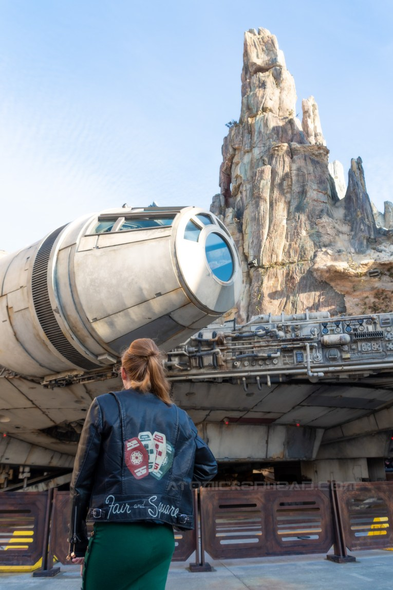 "Myself looking at the Millennium Falcon, the back of my jacket visible, which features red, green, and white cards with symbols on them, and text reading ""Fair and Square"" along the bottom."