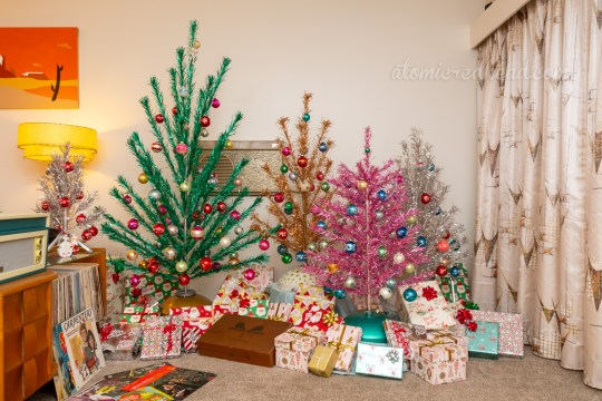 Our collection of aluminum Christmas trees huddle against a wall, a tall green tree, next to a shorter gold tree, pink tree and silver tree. The trees are covered with glass ball ornaments of various colors. Wrapped presents sit below.
