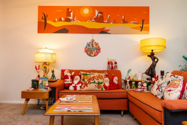 A view of the couch under the desert painting. Vintage Santa plushes sit on the couch.