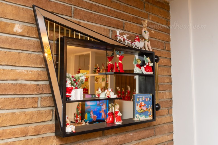 Close-up of the shadow box, which is black with mirror accents and features small ceramic figures of an angel, Santa, and a Little Golden Book for the story The Night Before Christmas.
