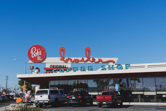 "Bob's, a large, long flat roof building, with a jutting pointed sign reading ""Bob's Big Boy Broiler"""