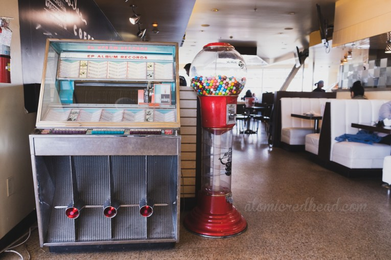 Inside, a vintage jukebox rests against white upholstered semicircle booths.