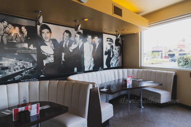 Black and white photos of Bob's employees through the years above white semicircle booths.