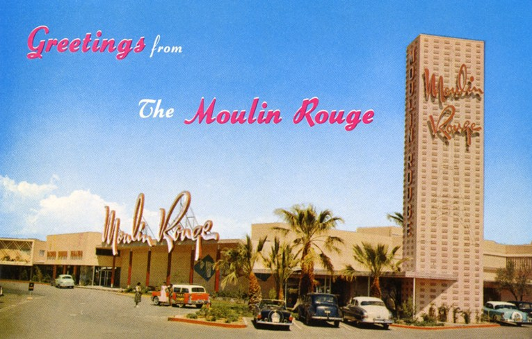 "The Moulin Rouge on a postcard from the period. A low roof building features towering script that reads ""Moulin Rouge."" A tall tower on the left also reads ""Moulin Rouge"" in neon, and also features a massive neon version fo the Eiffel Tower. Script across reads ""Greetings from the Moulin Rouge"""