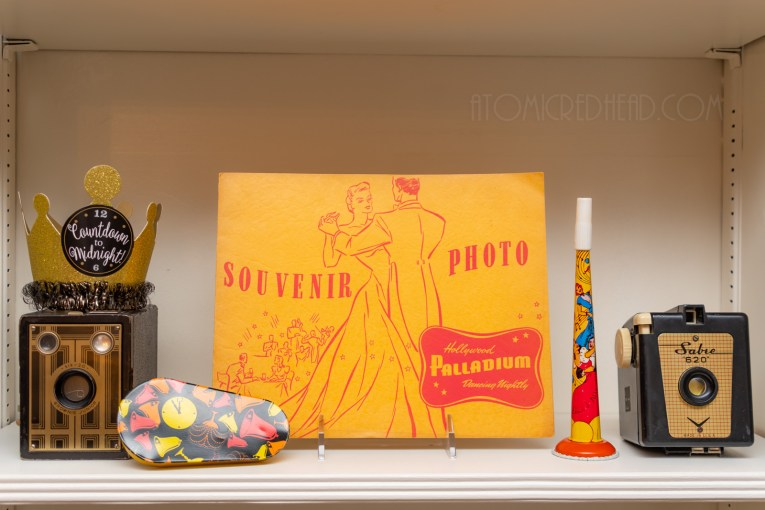 "A souvenir photo folder from the Hollywood Palladium features a dancing couple, it is flanked by two black and gold cameras, vintage noise makers, and a gold crown reading ""Countdown to Midnight"""