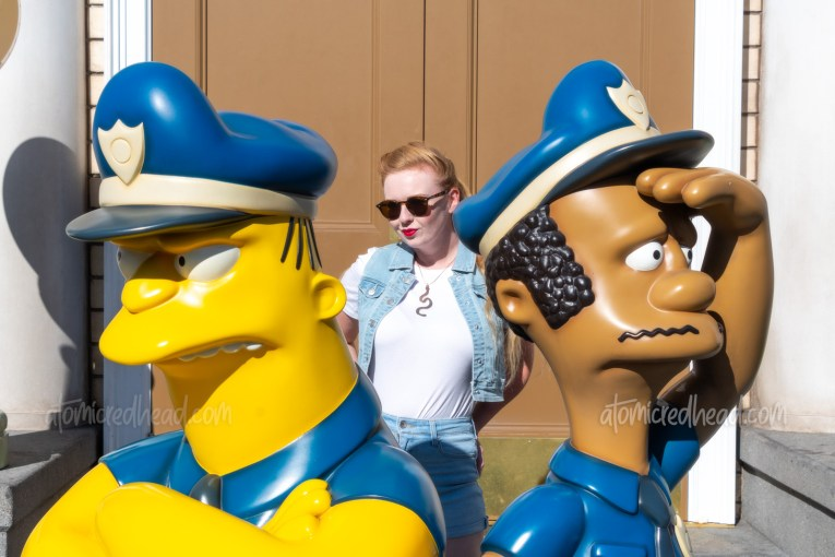 Myself, wearing a white t-shirt, with a jean vest over, and jean shorts, standing behind statues of Springfield's cops, Lou and Eddie.