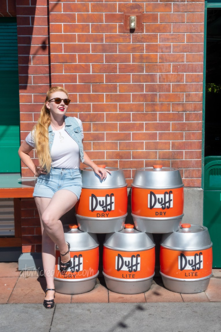 Myself, wearing a white t-shirt, with a jean vest over, and jean shorts, standing in front of topiaries of Duff beer kegs.