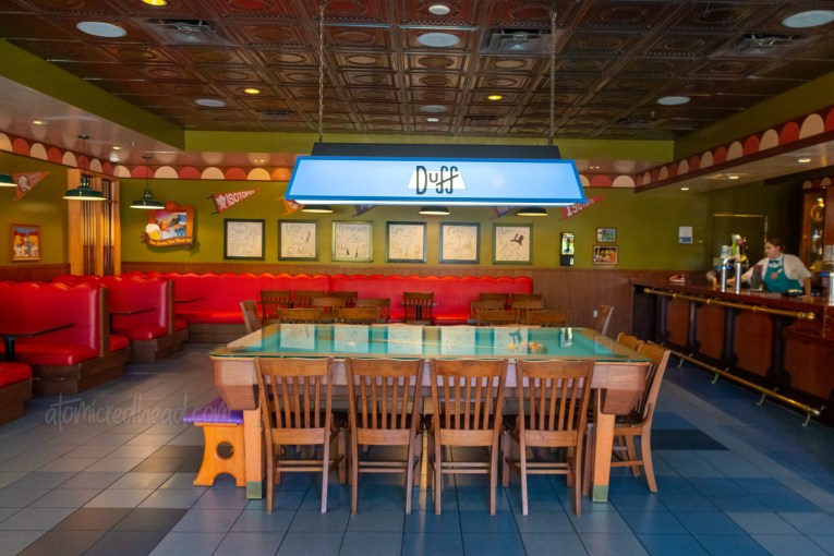 Inside Moe's Tavern, red leather booths, a pool table, and a bar sits off to the right.