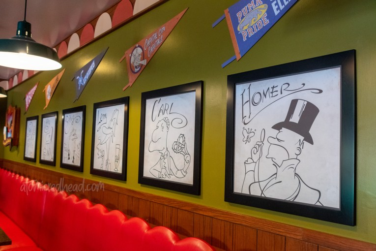 Cartoon illustrations of Homer and his buddies line the wall of Moe's.