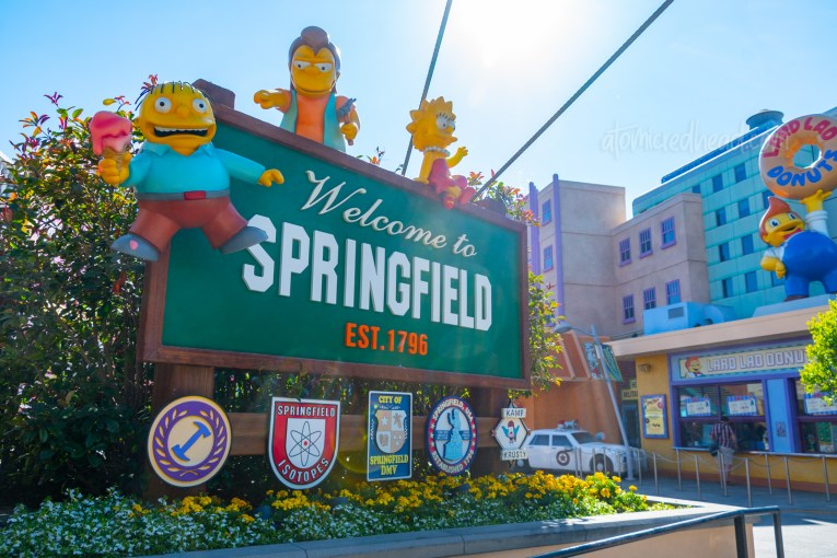 "A sign reads ""Welcome to Springfield"" and several of the children from the show hang and sit atop the sign."