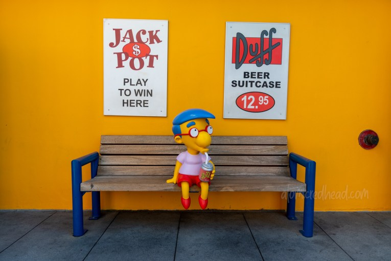Statue of Milhouse sits on a bench drinking a Buzz Cola.